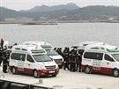 Vozy záchranářů v jihokorejském přístavu Džindo nakládají těla pasažérů, které...