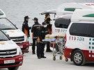 Záchranáři v jihokorejském přístavu Džindo nakládají dalšího mrtvého pasažéra z...