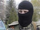 Maskovaný ozbrojený strážce s připnutou oranžovo-černou stuhou, která se stala symbolem proruské vzpoury na východě Ukrajiny.