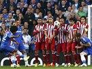 Willian z Chelsea zkouší vyzrát na brankáře Atlétika Madrid z přímého kopu. Zeď