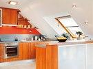 Kuchyňská deska poskytuje dostatečný pracovní prostor. Barový pult s dvířky z
