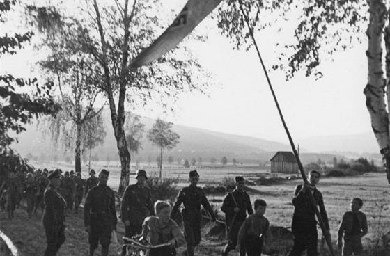Tři ozbrojení vojáci v čs. uniformách postupují jako místní průvodci na čele...