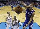 Blake Griffin z LA Clippers smečuje do koše Oklahoma City. Steven Adams (12) a...
