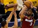 Míč nad hlavou drží  Dwyane Wade z Miami, pozorně ho střeží George Hil z