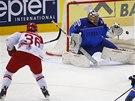 Dánský hokejista Jannik Hansen překonává italského brankáře Daniela Bellissima