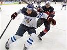 Finský hokejista Jyri Marttinen (vlevo) si kryje puk před americkým útočníkem...