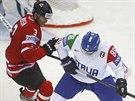 Kanadský hokejista Kevin Bieksa (vlevo) v souboji s Vincentem Roccem z Itálie.