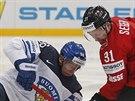 Erik Haula (vlevo) z Finska a Mathias Seger ze Švýcarska bojují o puk.