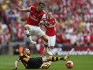 PŘESKOČÍM TĚ. Aaron Ramsey z Arsenalu (nahoře) se skluzem Davida Meylera z...
