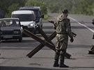 Proruský ozbrojenec stojí na silničním zátarasu nedaleko Slavjansku na trase do...