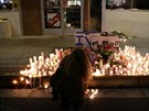 Dívka zapaluje svíčku na místě, kde zemřeli její spolužáci.