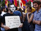 Mu� s maskou zobrazuj�c� �pan�lsk�ho premi�ra Mariana Rajoye dr�� transparent s...