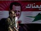 Syrští vojáci prochází kolem autobusu s portrétem autoritativního prezidenta...