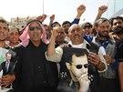 Syřani s obrázkem prezidenta Asada zpívají slogany při čekání na překročení...