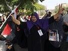 Jedna z podporovatelek Abdala Fattáha Sísího se raduje a tancuje před budovou...