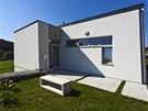 K vstupním dveřím do domu vede zpevněná betonová plocha, které dělá společnost