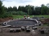 Slaměno-hliněný domeček stojí na kamenném kruhu.