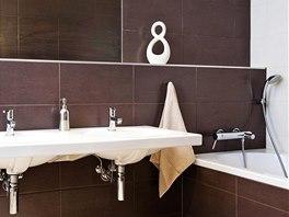 Tmavé obklady v hlavní koupelně působí velmi elegantně, zvláště v kombinaci se
