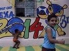 Dva malí kluci si hrají v ulicích Fortalezy. Malovánky na zdi signalizují, že...