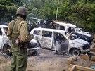 Keňský policista stojí u vraků aut, které zničili neznámí teroristé v Kibaoni...