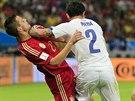 JAKO V HOKEJI. Chilan Eugenio Mena (v bílém) bojuje na hřišti o míč se Španělem...