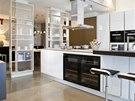 Kuchy� od ob�vac�ho pokoje odd�luj� police p��stupn� ��ste�n� z obou stran.