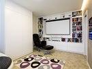 V obývacím pokoji nechybí plátno pro promítání. Bílá barva zvětšuje prostor.