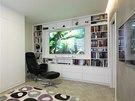 V obývacím pokoji nechybí plátno pro promítání. Pokud je stažené, září do prostoru LED obraz. Bílá barva zvětšuje prostor.