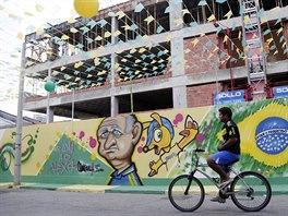 BEZ DRŽENÍ. Fanoušek projíždí na kole vyzdobenou ulicí ve Fortaleze. Na...