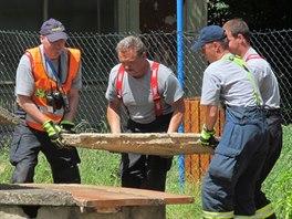 Hasiči zabezpečují studnu, do které v pondělí dopoledne spadli dva chlapci (16. června, 2014).