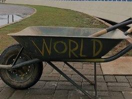 U hřiště stojí kolečko s rýčem. Na jedné straně má namalovaný nápis WORLD,...