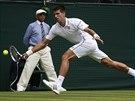 Novak Djokovič dobíhá míček v prvním kole Wimbledonu.
