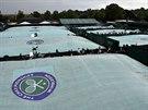 PLACHTY. Ve Wimbledonu při dešti tradičně zatahují nad travnatými kurty zelené...