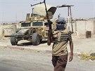 Ozbrojenec z ISIL stojí na stráži nedaleko rafinerie v Bajdží (19. června 2014).