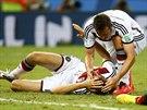 Německý útočník Miroslav Klose se ptá Thomase Müllera, který má roztržené...