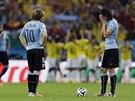 Uruguayští fotbalisté smutně sledují kolumbijské oslavy.