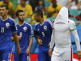 NEJDE NÁM TO. Zklamaný Íráčan Andranik Teymourian ukrývá svou hlavu do dresu ve chvíli, kdy Bosňan Miralem Pjanič (na snímku mezi Džekem a Ibiševičem) slaví svůj gól, jímž upravil skóre na 2:0.