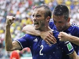 ZÁVĚREČNÁ BRANKA. Bosňan Avdija Vršajevič (v objetí Vedada Ibiševiče) slaví svůj gól, jímž pečetil výhru týmu 3:1 nad Íránem v závěrečném zápase na mistrovství světa v Brazílii.