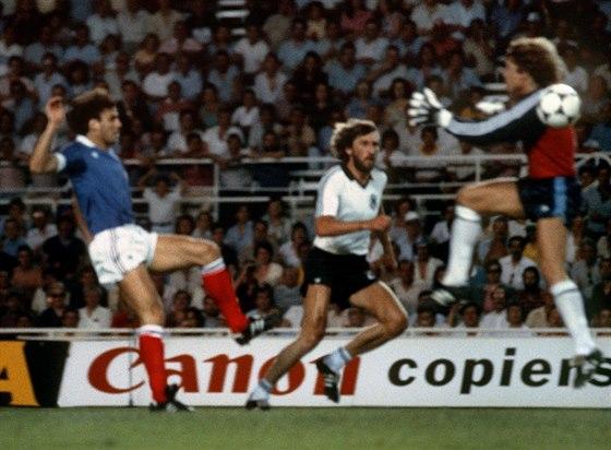 Německý brankář Harald Schumacher skáče proti francouzskému soupeři Patricku...