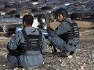 Afghánští policisté sledují ohořelé kamiony na předměstí Kábulu po útoku...