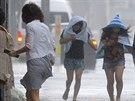 Ženy jdou na okinawské silnici Naha v silném větru, na Okinawu se blíží tajfun...