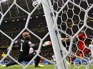 Americký brankář  Tim Howard se ohlíží za míčem po střele belgického útočníka...
