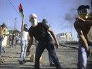 Palestinec hází kámeny na izraelské policisty během pohřbu chlapce uneseného z...