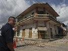 Mexický policista hlídkuje před domem ve městě Huixtla, který citelně poškodilo...