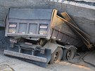 Nákladní vůz se pod vahou trosek vyloženě propadl do vozovky.