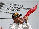 Lewis Hamilton se tulí k trofeji pro vítěze Velké ceny Británie.
