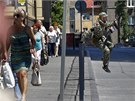 Proruský ozbrojenec přeskakuje zábradlí v doněcké ulici, kde probíhají boje