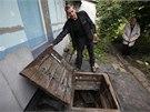 Obyvatel východoukrajinského Doněcku ukazuje dvířka do sklepa, který mu sloužil