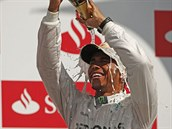 ŠTĚSTÍ. Britský pilot Lewis Hamilton se polévá šumivým vínem po vítězství ve...