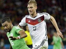 Německý obránce Per Mertesacker (vpravo) stíhá alžírského útočníka Arbí Hilál...